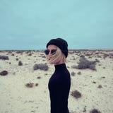 Stilvolles Mädchen im schwarzen Kleid auf Hintergrund der Wüste Stockbilder
