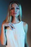 Stilvolles Modefoto des schönen dünnen vorbildlichen Porträts in einer weißen Klage mit dem geraden blonden Haar, das im Studio a Stockfoto