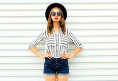 Stilvolles Modell der jungen Frau im schwarzen runden Hut, kurze Hosen, weißes gestreiftes Hemd, das auf weißer Wand aufwirft lizenzfreies stockfoto