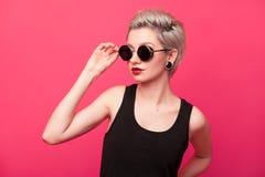 Stilvolles Modeporträt der jungen Frau auf rosa Hintergrund Stockbilder