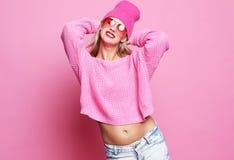 Stilvolles Modeporträt der modischen zufälligen jungen Frau im rosa pulover und im Hut, werfend über rosa Hintergrund auf Stockfotos