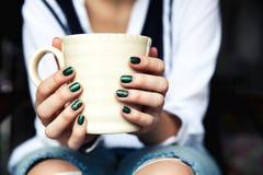 Stilvolles modernes Mädchen mit einem Tasse Kaffee und einer grünen Maniküre in den Jeans Mode, Sorgfalt, Schönheit stockfotografie