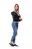 Stilvolles modernes Modemädchen in den Jeans und in Lederjacke, die hinten über der Schulter schauen Stockfotografie
