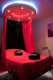 Stilvolles rotes Bett mit Schwarzem pillows Kabinendach Stockfotografie