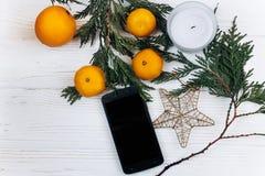 Stilvolles Telefon mit leeren Schirm- und Weihnachtsorangen und Goldenem Stockbild