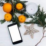 Stilvolles Telefon mit leeren Schirm- und Weihnachtsorangen und Goldenem Lizenzfreies Stockfoto