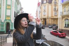 Stilvolles touristisches Mädchen fotografiert die Architektur der alten Stadt am Telefon Lizenzfreie Stockbilder