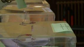 Stimmzettel und Wahlurnen im Wahllokal, vier Schüsse