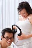 Stimulating the fetus using music. Chinese couple stimulating the fetus using music with headset Royalty Free Stock Image