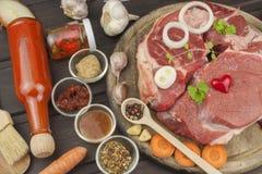 Stinco e verdure crudi del manzo Vendite di manzo Preparando carne per cucinare Carne cruda su un tagliere pronto per tagliare Fotografia Stock Libera da Diritti