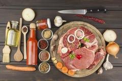 Stinco e verdure crudi del manzo Vendite di manzo Preparando carne per cucinare Carne cruda su un tagliere pronto per tagliare Immagine Stock