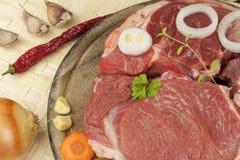 Stinco e verdure crudi del manzo Vendite di manzo Preparando carne per cucinare Carne cruda su un tagliere pronto per tagliare Immagini Stock Libere da Diritti