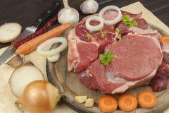 Stinco e verdure crudi del manzo Vendite di manzo Preparando carne per cucinare Carne cruda su un tagliere pronto per tagliare Fotografia Stock