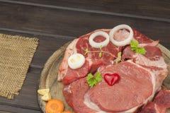 Stinco e verdure crudi del manzo Vendite di manzo Preparando carne per cucinare Carne cruda su un tagliere pronto per tagliare Fotografie Stock Libere da Diritti