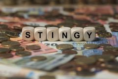Stingy - cube with letters, money sector terms - sign with wooden cubes Royalty Free Stock Image