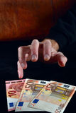 Stingy hand reaches for euro money. Greedy hand reaches for euro money. Image in low key Stock Images