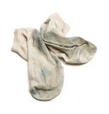 Stinkande smutsiga sockor som isoleras på den vita bakgrunden Arkivfoto