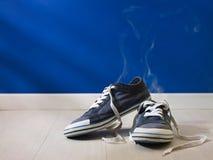 Stinkende abgedroschene Schuhe verließen auf hölzernem Fußboden Stockfoto