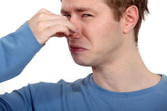 It stinks!. Man holding his finger to his nose to avoid bad smell Royalty Free Stock Photography