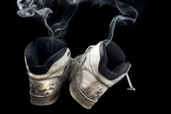 Stinky sneakers. Pair of rotten old sneakers on a black background Royalty Free Stock Image