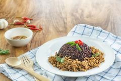 Stir fried basil with minced pork and berry rice in a plate on a wooden table. Stir fried minced pork basil and berry rice in a dish and chili fish sauce Ready stock image