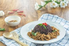 Stir fried basil with minced pork and berry rice in a plate on a wooden table. Stir fried minced pork basil and berry rice in a dish and chili fish sauce Ready stock photo