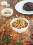 Stir fried basil with minced pork in a bowl and rice berries on the plate. put on a wooden table. Stir fried basil with minced pork in a bowl and rice berries on royalty free stock images