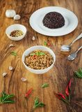 Stir fried basil with minced pork in a bowl and rice berries on the plate. put on a wooden table. Stir fried basil with minced pork in a bowl and rice berries on stock image