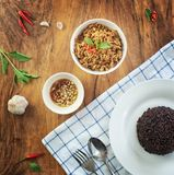 Stir fried basil with minced pork in a bowl and rice berries on the plate. put on a wooden table, top view. Stir fried basil with minced pork in a bowl and rice royalty free stock image