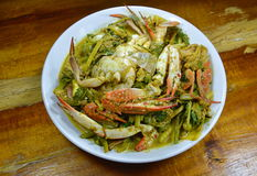 Stir fried blue swimmer crab in yellow curry on dish. Stir fried blue swimmer crab in yellow curry on white dish Stock Photography