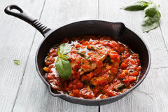 Stir-fried chicken breast in a sauce of tomatoes, garlic, basil and olive oil. Black cast-iron pan, light wooden table Stock Photo