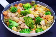 Stir fried chicken fillet with vegetables and pasta in a frying pan on a black abstract background Stock Photography