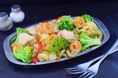 Stir fried chicken fillet with vegetables and pasta on a metal tray on a black abstract background Royalty Free Stock Image
