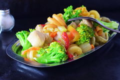Stir fried chicken fillet with vegetables and pasta on a metal tray on a black abstract background Royalty Free Stock Photo