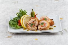 Stir fried chicken wrap with carrot. scallion and radish served with sliced lemon, tomato and lettuce in white ceramic plate. Stir fried chicken wrap with Royalty Free Stock Photography