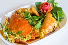 Stir-fried crab with curry powder and fried egg. In white dish on table Stock Image