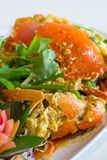 Stir-fried crab with curry powder and fried egg. In white dish on table Stock Photos