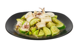 Stir fried cucumber vegetable with squid on plate isolated on wh Royalty Free Stock Photos
