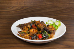 Stir fried deep fried catfish with curry past Stock Photo