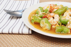 Stir fried gourd with shrimp and egg. On plate and brown plate mat royalty free stock photo
