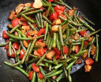 Stir fried green beans and peppers. Stirfried green beans with red pepper, ginger and tempeh in black wok, tumis boentjes Stock Image