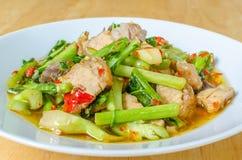 Stir fried kale with crispy pork Stock Photos