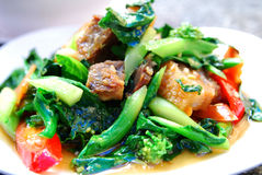 Stir fried kale with crispy pork Stock Images