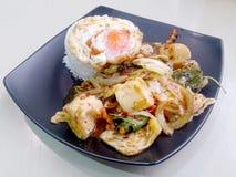 Stir Fried mezcló verduras con Chili Paste asado, el huevo frito y el arroz tailandés del jazmín en plato negro Comida vegetarian Fotos de archivo