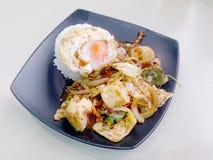 Stir Fried mezcló verduras con Chili Paste asado, el huevo frito y el arroz tailandés del jazmín en plato negro Comida vegetarian Imagenes de archivo