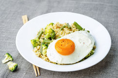 Stir fried millet with broccoli, green beans and fried egg Royalty Free Stock Photo