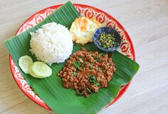 Free Stir-fried Minced Pork With Basil Leaves Served With Rice And Fried Egg On Banana Leaf On Zinc Tray Over Wooden Table Background Royalty Free Stock Photo - 188341045