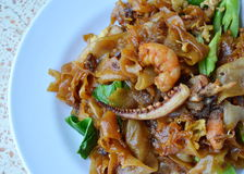 Stir-fried noodle with seafood in black soy sauce. On plate royalty free stock photography
