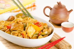 Stir-fried noodles with chicken and vegetables served in a bowl, Stock Image