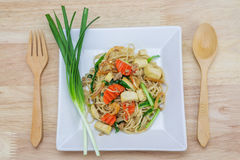 Stir-fried noodles, Chinese style. On wooden background royalty free stock photo